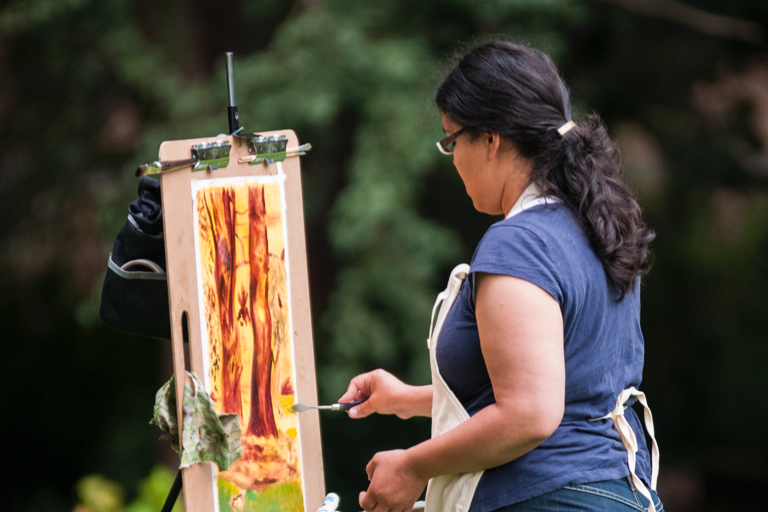 Student painting at an easel outdoors