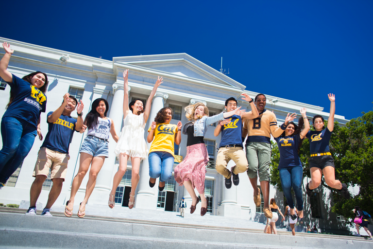 Large group of students jumping on the steps in front of a grand building