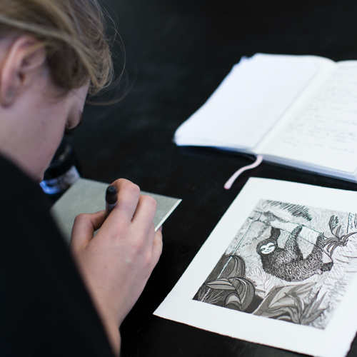 Student drawing intricate ink drawing