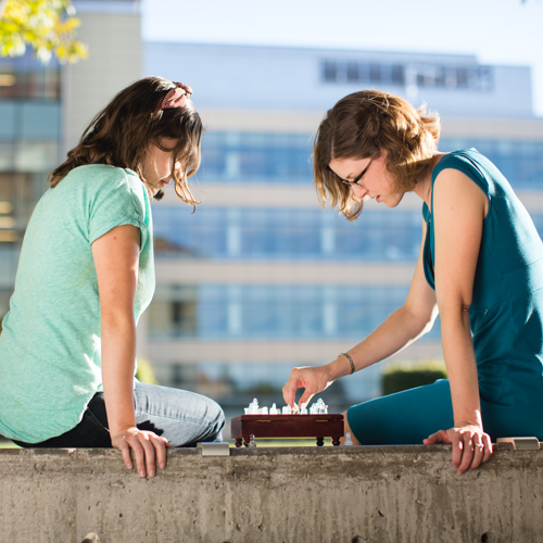 Two female students playing chess