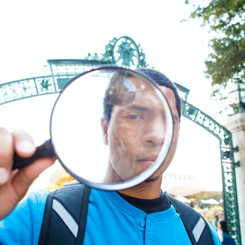 Student with a magnifying glass in front of Sather Gate