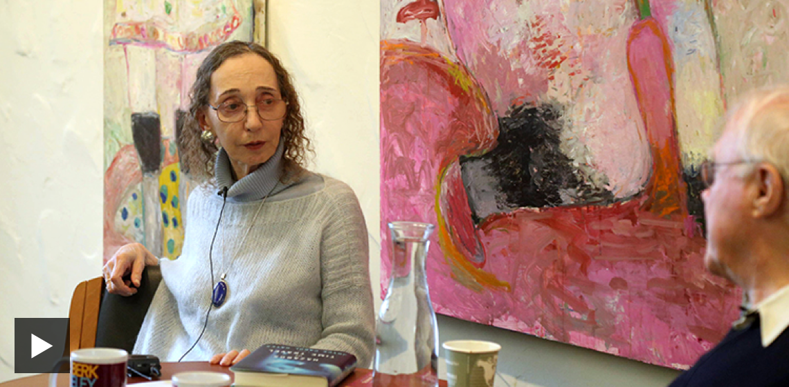 Joyce Carol Oates sits in front of a pink painting, in conversation with a man in profile.