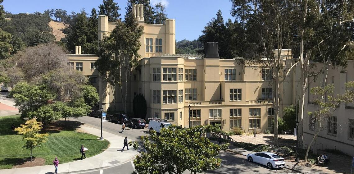 Image of Stephens Hall on UC Berkeley campus, beige castle like structure surrounded by trees on bright sunny day.